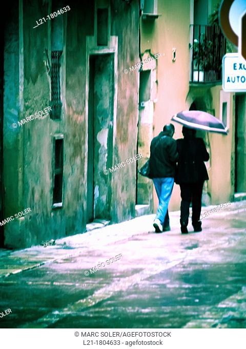 Couple under an umbrella, street. Tarragona, Catalonia, Spain