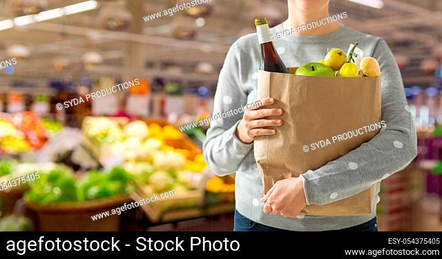 close up of woman with paper bag full of food