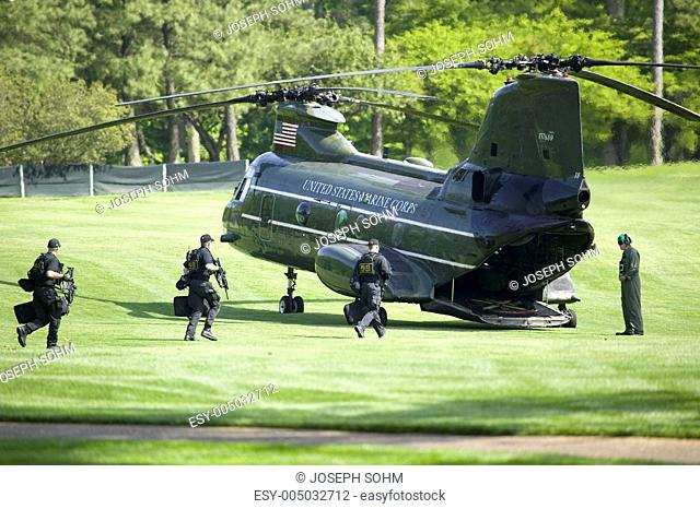 Secret Service guards running to Presidential Helicopter for takeoff on green golf course in Williamsburg, Virginia, May 4, 2007