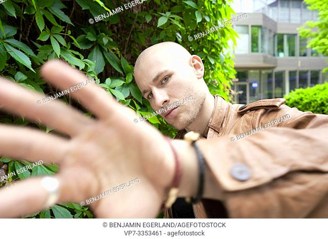 man in front of plants in city