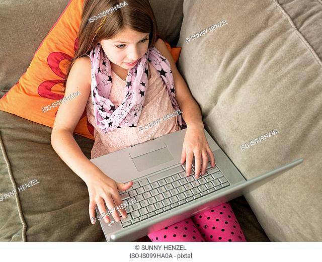 Girl using laptop on sofa, elevated view