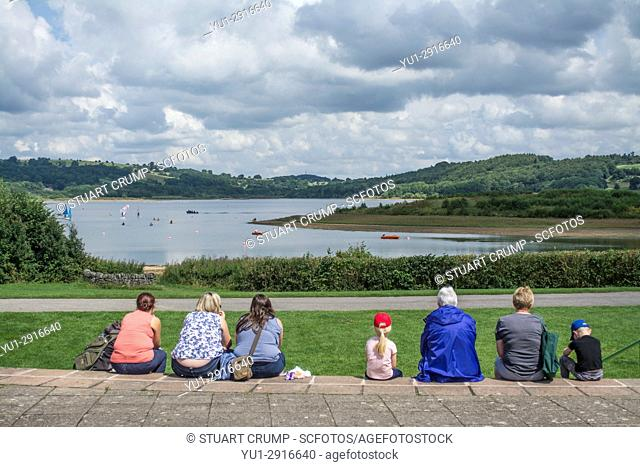 Visitors sitting on steps looking over the resevoir at Carsington Water in Derbyshire UK