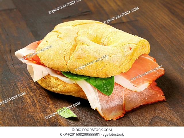 Ring-shaped bread roll (friselle) with slices of Schwarzwald ham