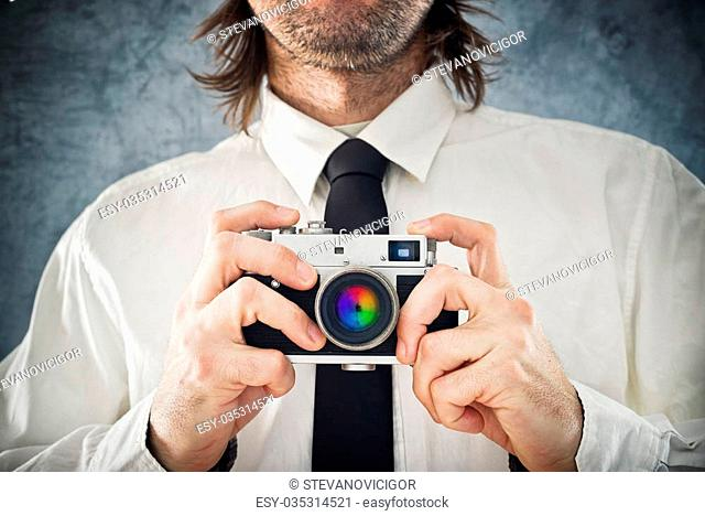 Businessman taking picture with retro style photo camera