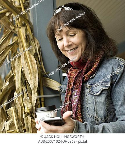 Mature woman looking at a mobile phone and smiling