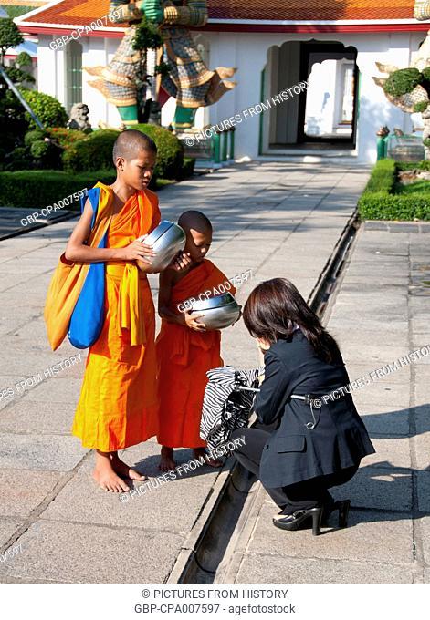 Thailand: Giving alms to novice monks at Wat Arun (Temple of Dawn), Bangkok