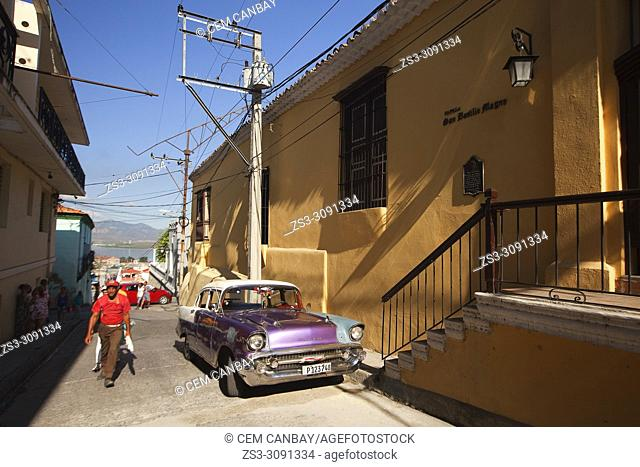 Scene from the historic center with an old American car parked at the street side in the foreground, Santiago de Cuba, Central America