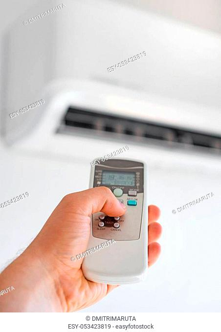 Hand holding remote control aimed at the air conditioner