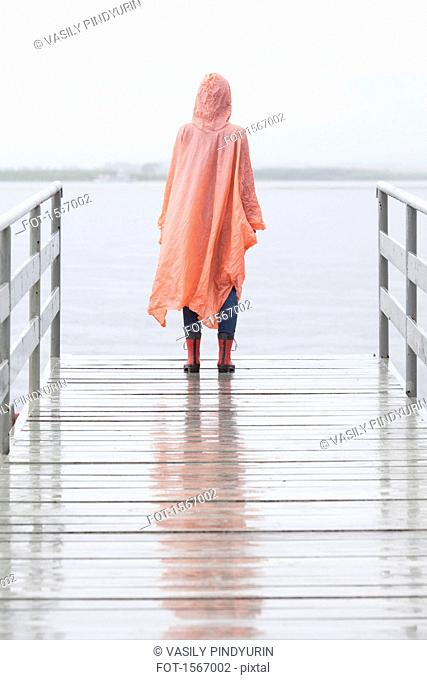 Rear view of woman wearing raincoat standing on jetty during rainy season