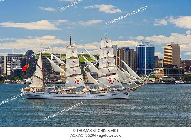 Tall Ship Sagres from Portugal cruises by Halifax skyline in Parade of Sail during Tall Ships Nova Scotia festival, Halifax, NS, Canada
