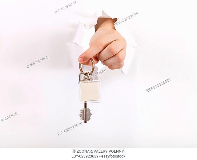 hand holds the key through a hole