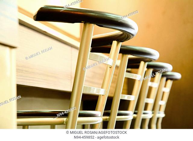 Stools lined up against the bar of a restaurant