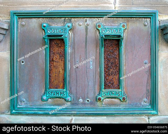 old british postal mail boxes with rusted letter slots and ornate green copper frames with the words postage stamps surrounded by an old stained metal frame in...