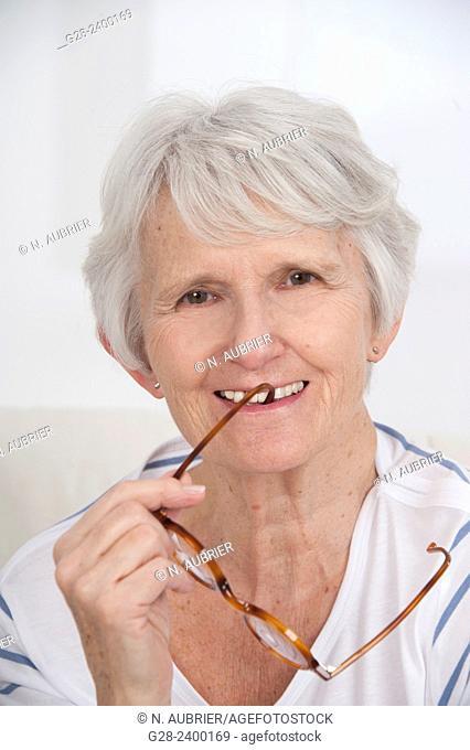 Portrait of beautiful senior woman holding glasses