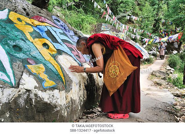 Tibetan monk pray at mani stone
