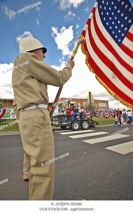 Member of a color guard carrying an American flag, in Lima Montana
