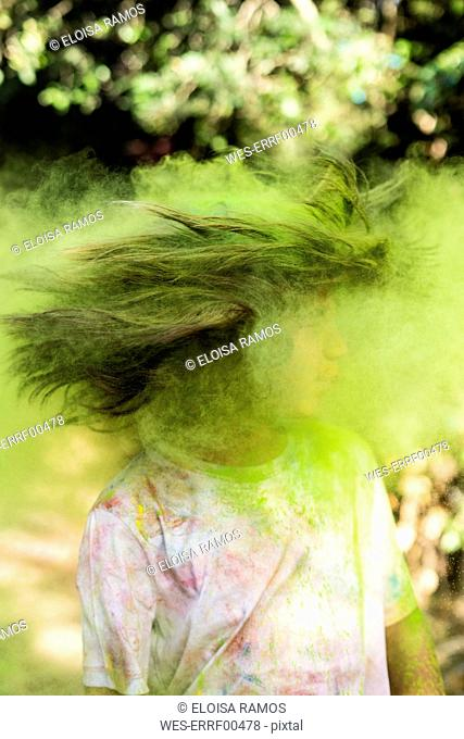 Boy shaking his head, full of colorful powder paint, celebrating Holi, Festival of Colors