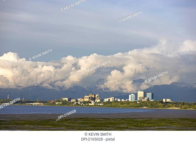 Late Afternoon Light Shines Through Clouds Onto The Downtown Anchorage Skyline After A Thunderstorm, Southcentral Alaska, Summer