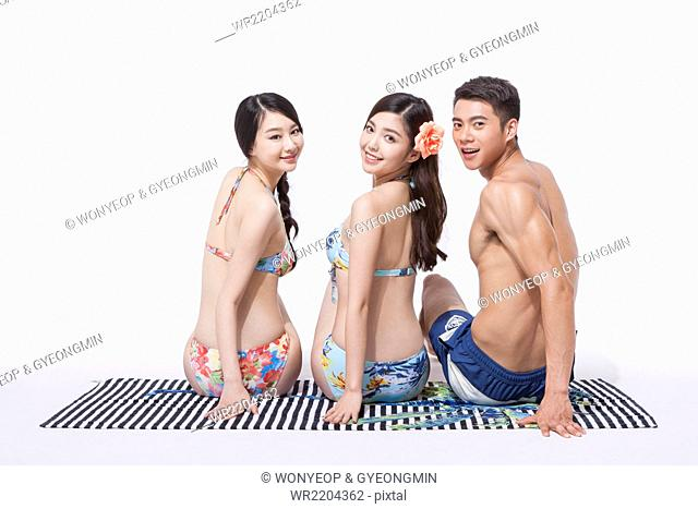 Back appearance of two women in bikini and a man in swimming pants sitting down on a towel together and looking back