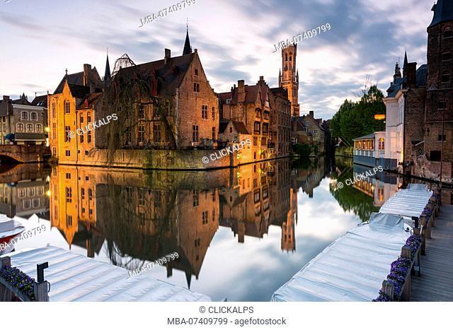 The medieval Belfry and historic buildings reflected in Rozenhoedkaai canal at dusk, Bruges, flemish region, West Flanders, Belgium, Europe
