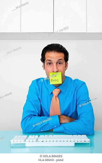 Portrait of a businessman with an adhesive note on his mouth