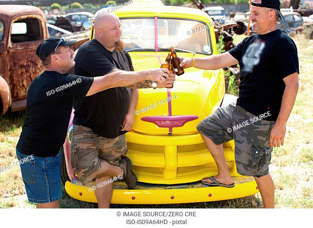 Men drinking beer by colorful car