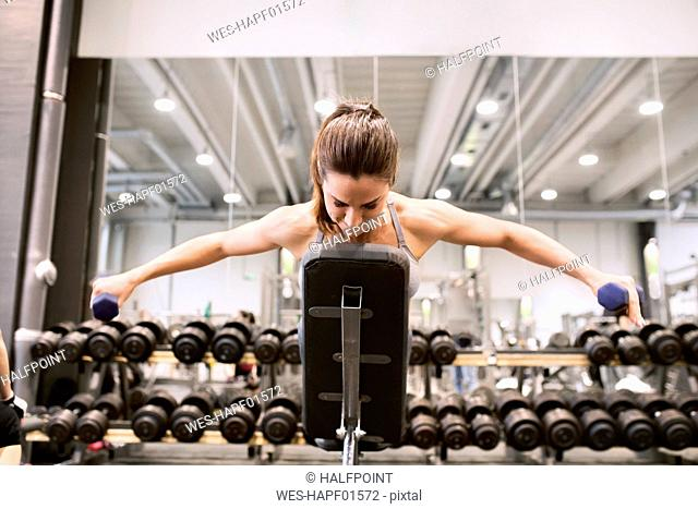 Young woman exercising with dumbbells in gym