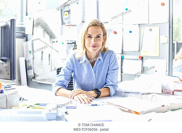 Portrait of confident woman sitting at desk in office surrounded by paperwork