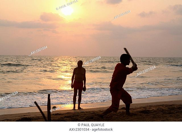 Playing cricket, the national sport of India, on Anjuna Beach at sunset, Goa State, India, Asia