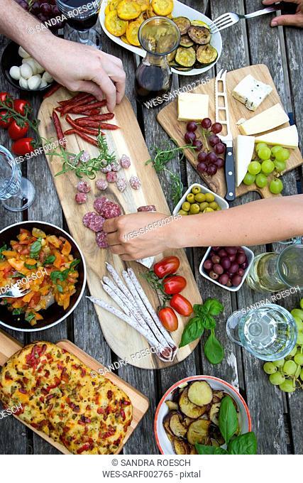 People enjoying variety of Mediterranean antipasti