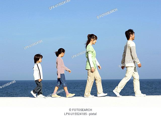 Family walking single file along the beach