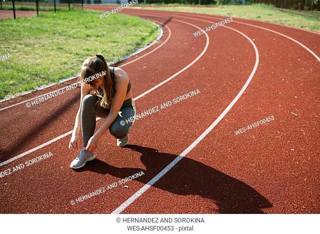 Sportswoman on racetrack tying shoes