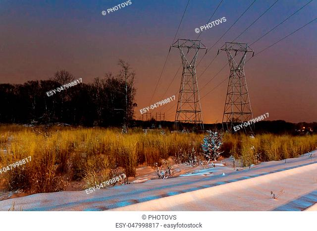Industrial landscape - illuminated railway station by winter night with snowfall Winter night road power lines