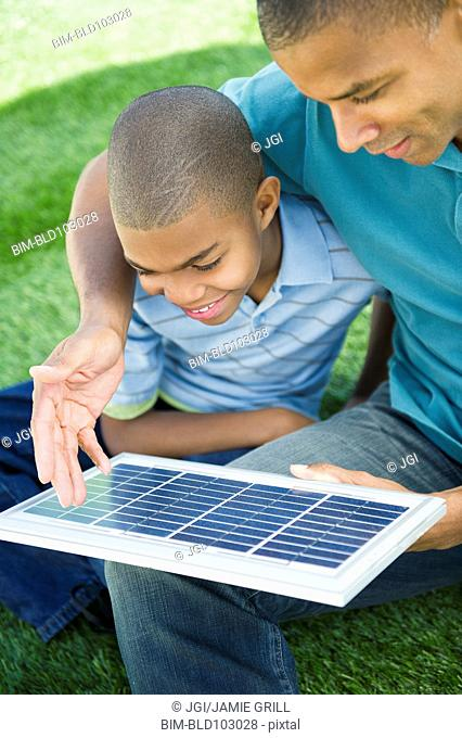 Father and son looking at solar panel
