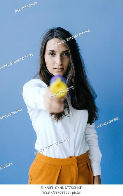 Pretty young woman shooting with a confetti gun