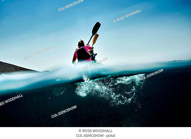 Teenage boy and mother sea kayaking, surface level rear view, Limnos, Khios, Greece