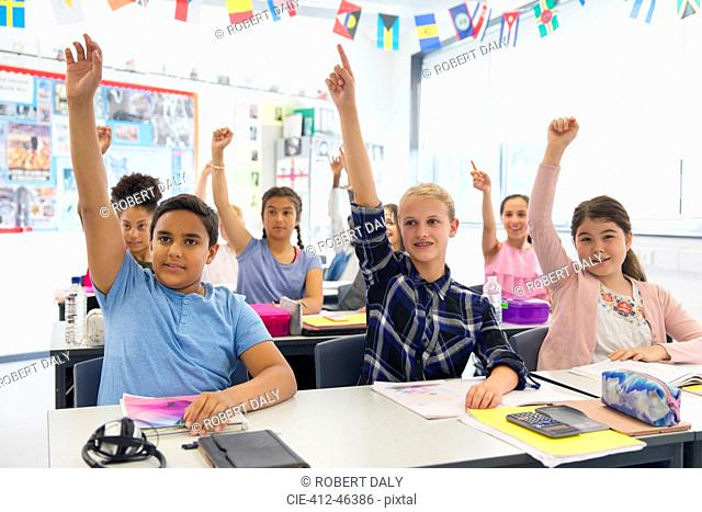 Eager junior high school students with hands raised in classroom
