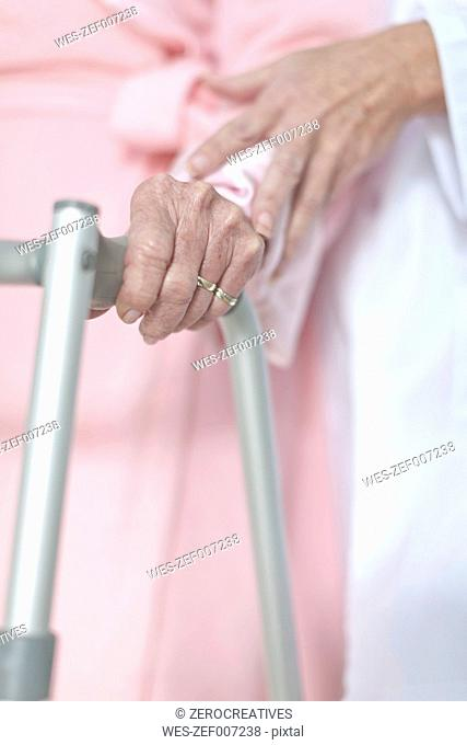 Elderly patient with walking frame being supported