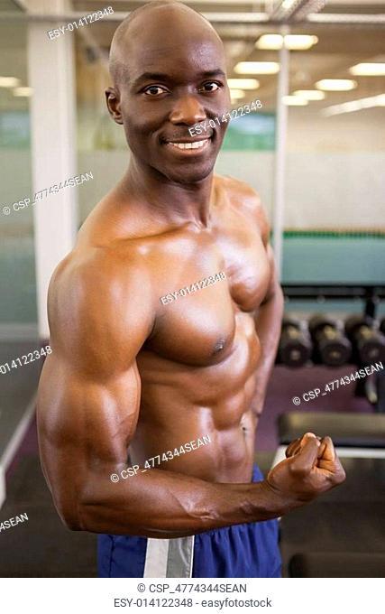 Smiling shirtless muscular man posi