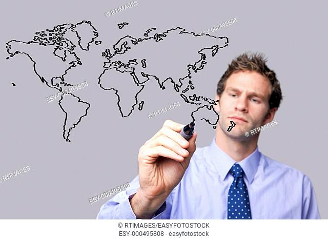 Businessman drawing a map of the world on a glass screen  The background is a uniform color all over so you can increase the copy space easily  Focus is on his...