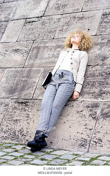 Fashionable blond woman with folder leaning against wall having a rest
