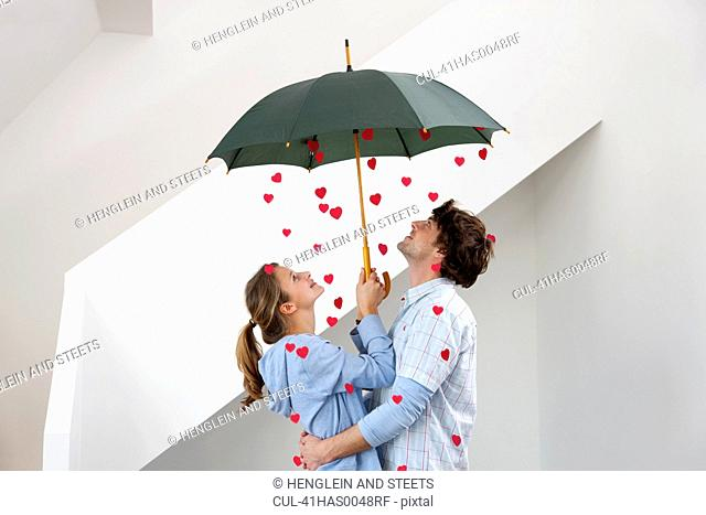 Couple standing under shower of hearts