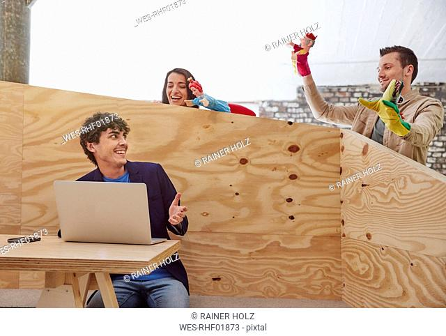 Young businessman working on laptop with colleagues playing hand puppets behind wooden wall
