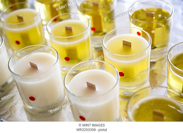 High angle close up of handmade white and yellow jar candles with wooden wick