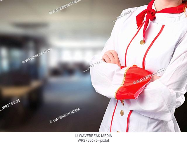Chef arms folded against blurry restaurant