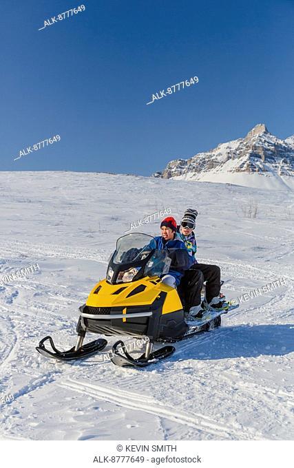 Snowboarders riding on a snowmachine, Anaktuvuk Pass, Winter, Gates of the Arctic National Park, Brooks Range, Arctic Alaska