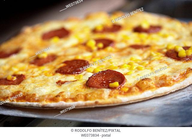 Pepperoni and Corn Pizza getting out of the oven