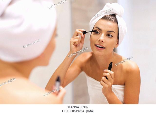 Beautiful woman using mascara in bathroom. Debica, Poland