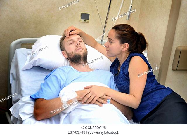 young sick man lying in bed at hospital room after suffering accident having his worried and caring wife or girlfriend together holding his hand giving him love...
