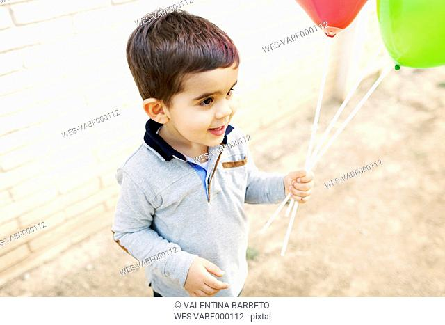 Toddler holding balloons